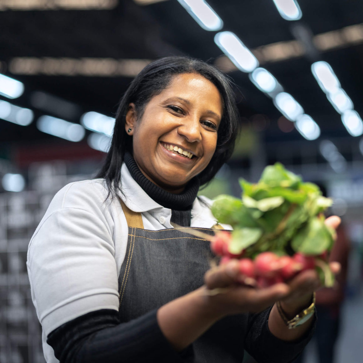 A woman at work at a grocery store, holding fresh produce and smiling.