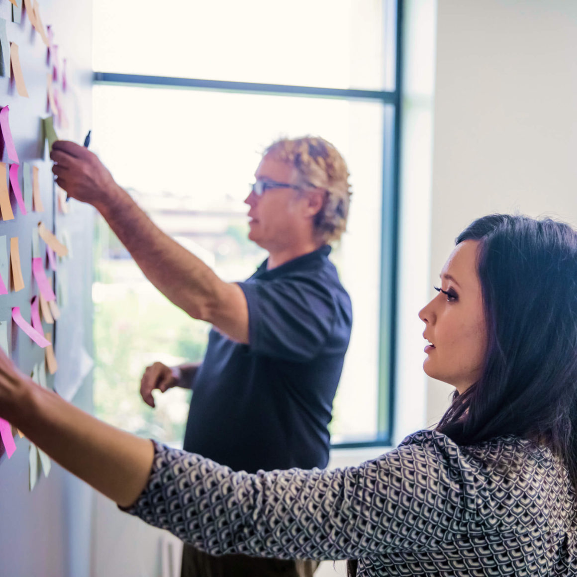A man and woman in a conference room, sticking post-it notes on a whiteboard.