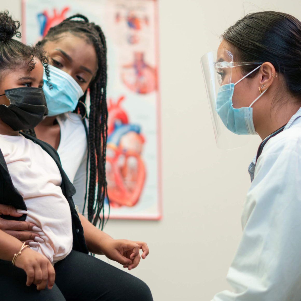 A woman and her daughter, wearing face-masks, talking to a doctor who is also wearing a face-mask.