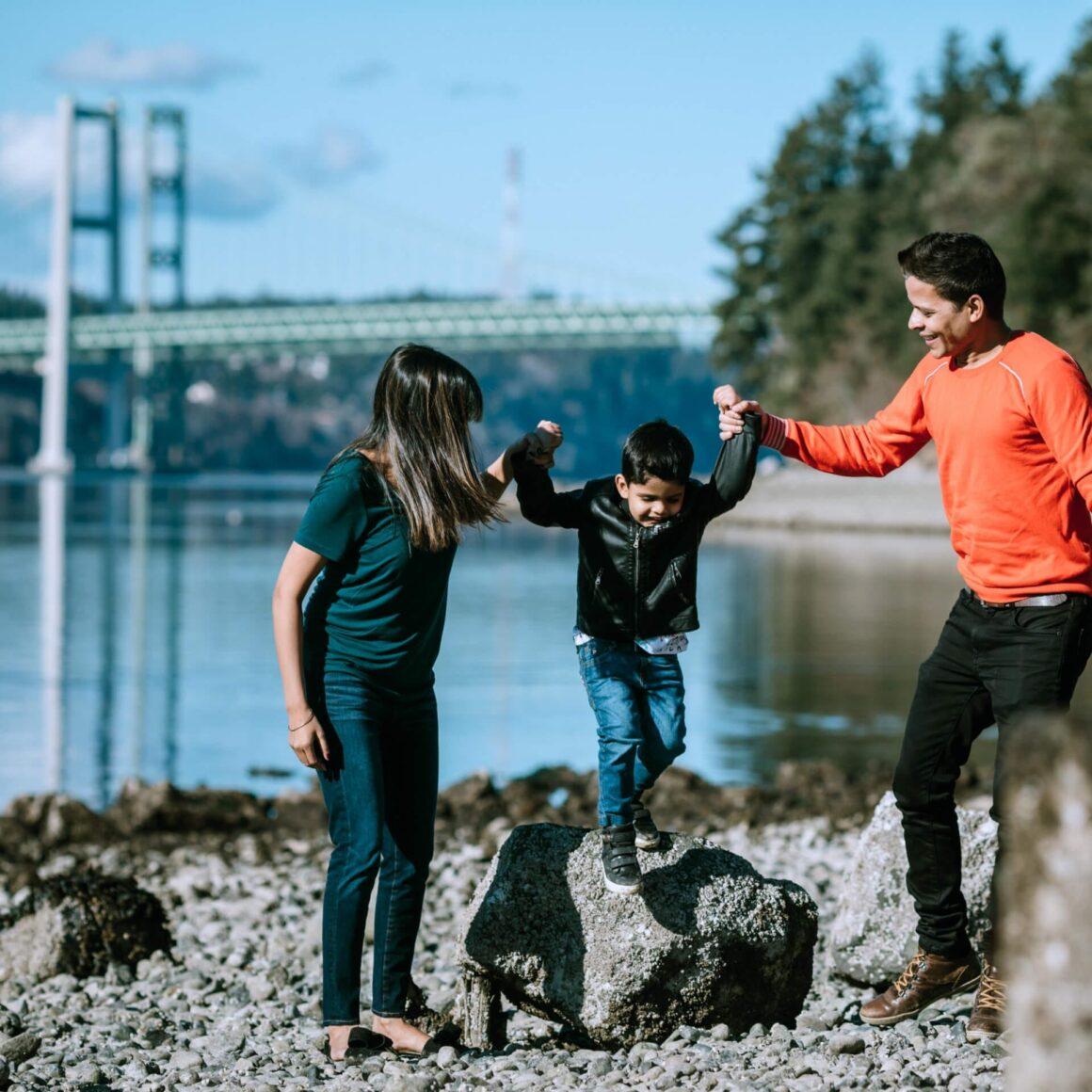A family walking near a lake.  Having a fun day out.